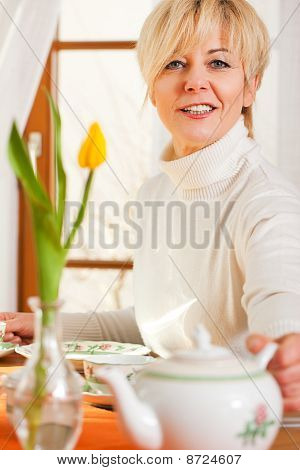 Woman grabbing coffee or tea pot
