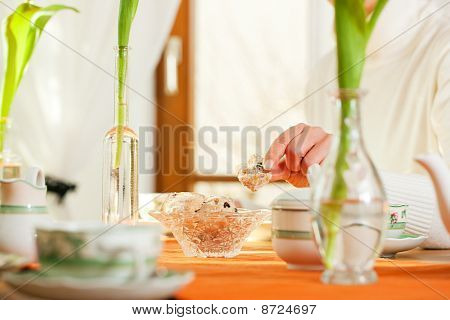 Woman taking cookies from coffee table