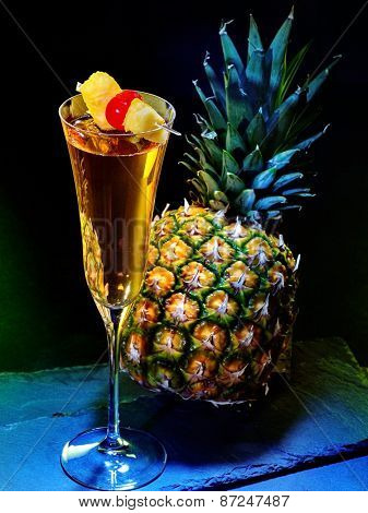 Champagne  cocktail with cherry and whole pineapple with leaves .