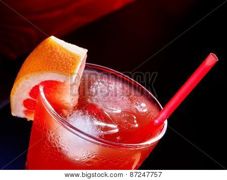 Red drink  with grapefruit and cube ice on dark background. Top view.