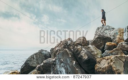 Woman Standing On Stone Near The Sea