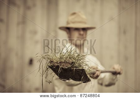 Farmer With A Shovel Full Of Grass