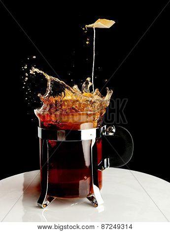 Tea bag falling in a cup of tea making a big splash