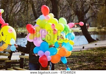 Woman Sells Colorful Balloons In The Park. Tinted Image