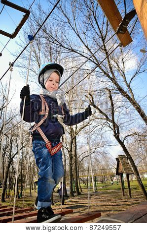 Boy Going On Suspension Bridge And Looking Down. Vertical