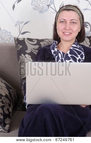 Woman using laptop sitting on cosy sofa