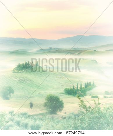 Dawn in a misty valley with view on a farmhouse in the hills near Pienza