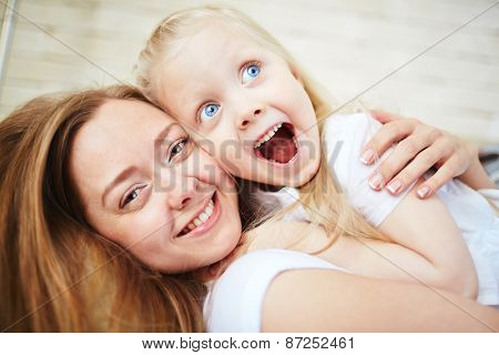 Affectionate female embracing her amazed little daughter