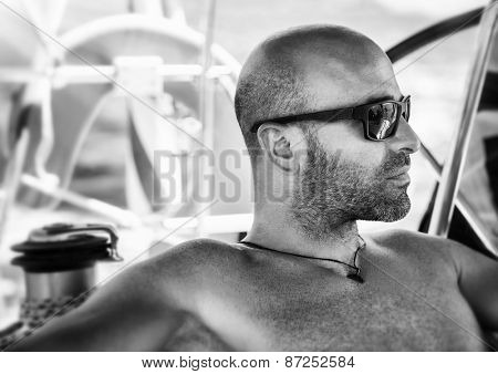 Closeup black and white portrait of sexy handsome man relaxing on sailboat, wearing stylish sunglasses, fashion and vogue concept