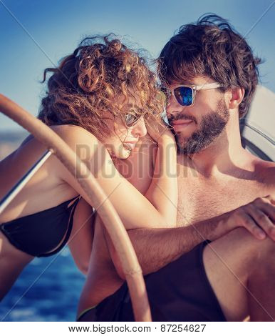 Portrait of a cute happy couple sitting on sailboat and enjoying bright summer day, enjoying romantic honeymoon vacation, love and travel concept
