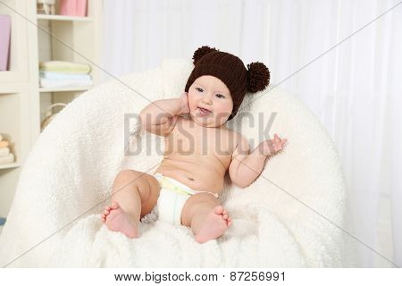 Cute baby girl in diapers sitting in arm-chair, on home interior background