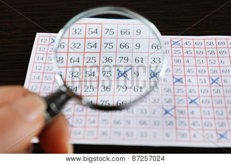 Female hand with magnifier analyzing lottery ticket, closeup