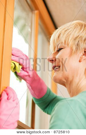 housewife cleaning her windows in rubber gloves