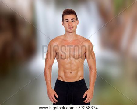 Handsome guy in bathing suit with an unfocused waterfall background