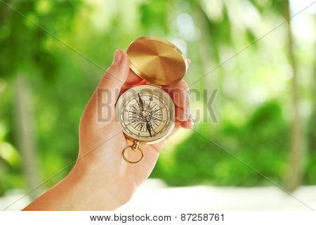Human hand with compass on nature background