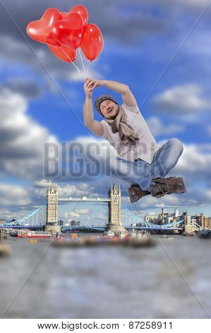 Young man flying on balloons with Tower bridge, London in background