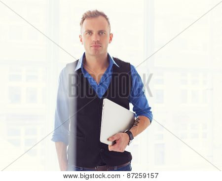 Young creative man holding laptop computer