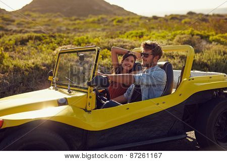 Happy Young Couple On A Road Trip In Beach Buggy