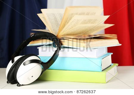 Books and headphones on French flag background
