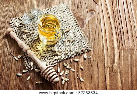 Honey In A Glass Jar With Wooden Dipper