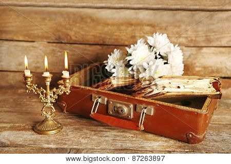 Old wooden suitcase with old books and flowers on wooden background