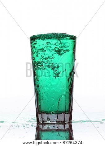 Glass of splashing Turquoise lemonade isolated on white background