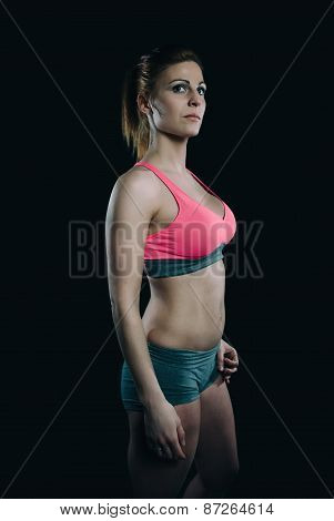 Athletic redhead woman with pink top over dark background