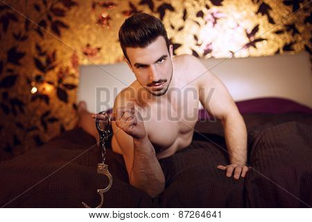 Sexy Macho Man Laying On Bed With Handcuffs