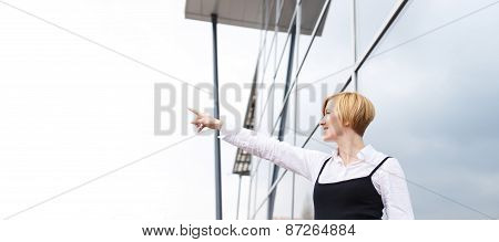 Blonde Businesswoman Pointing To Sky At Financial Center