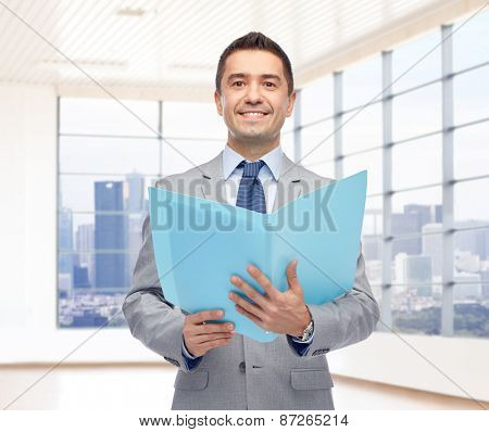 business, people, finances and real estate concept - happy smiling businessman in suit holding open folder over office room with big window and city view background