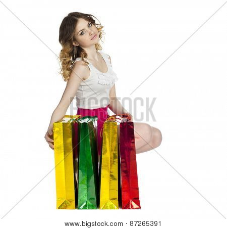 Full portrait of smiling young blonde girl with colorful shopping bags in red skirt posing on a white background