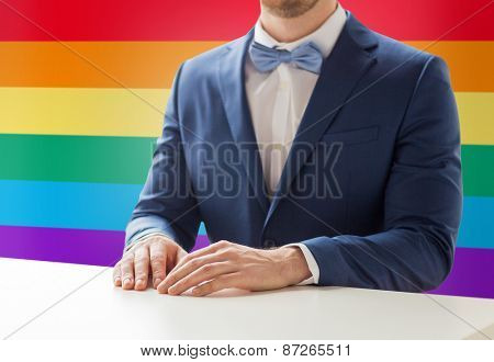 people, gay, wedding and same-sex marriage concept - close up of best man or groom in suit and bow-tie at table over rainbow flag background