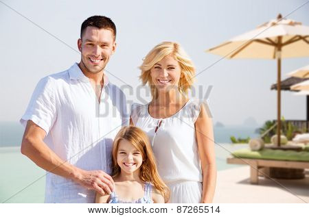 summer holidays, travel, tourism and people concept - happy family on vacation over resort beach background