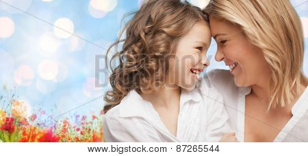 people, family, love and harmony concept - happy mother and daughter cuddling over blue sky and poppy field n background