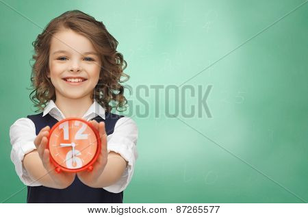 people, childhood, time and punctuality concept - happy girl with alarm clock over green chalk board background
