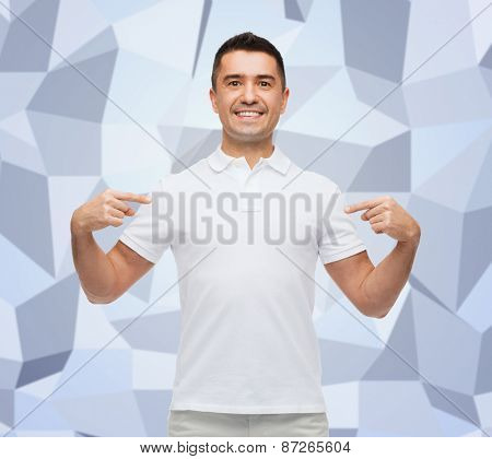 happiness, advertisement, fashion, gesture and people concept - smiling man in t-shirt pointing fingers on himself over gray graphic low poly background