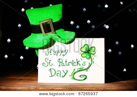 Greeting card for Saint Patrick's Day with leprechaun hat on wooden table on dark lights background