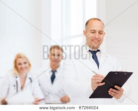 medicine, profession, teamwork and healthcare concept - smiling male doctor with clipboard writing prescription over group of medics