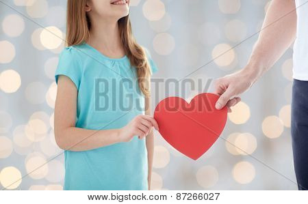 people, love, charity, holidays and family concept - close up of girl and male hand holding red heart shape over lights background
