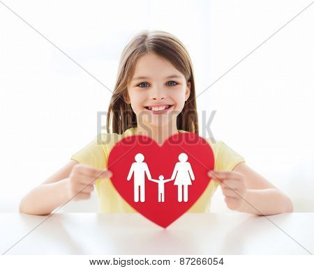 love, home, happiness and adoption concept - smiling little girl with red heart and family picture at home