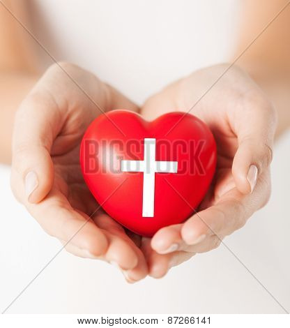 religion, christianity and charity concept - female hands holding red heart with christian cross symbol