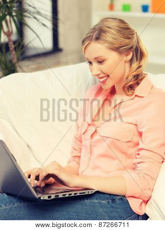 happy woman with laptop typing  at home