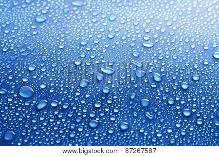 Water drops on glass on blue background