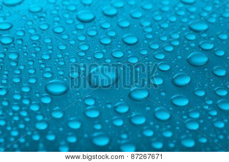 Water drops on glass on light background