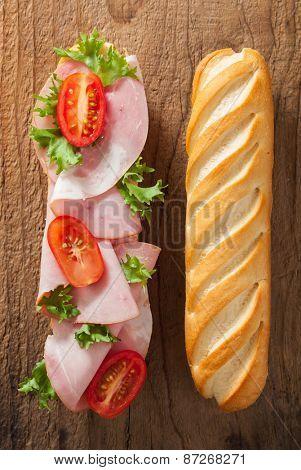 long baguette sandwich with ham tomato lettuce