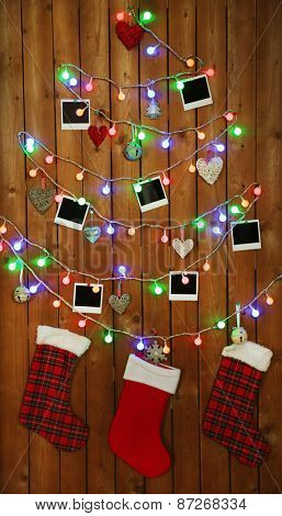Garland in shape of Christmas tree with retro blank photos on wooden wall background