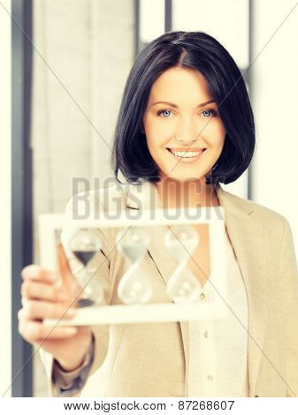 picture of attractive businesswoman holding hourglass.
