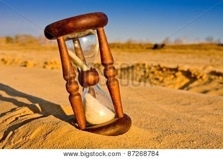 hourglass in desert sandy surface