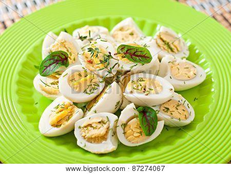 Boiled quail eggs halves on a green plate