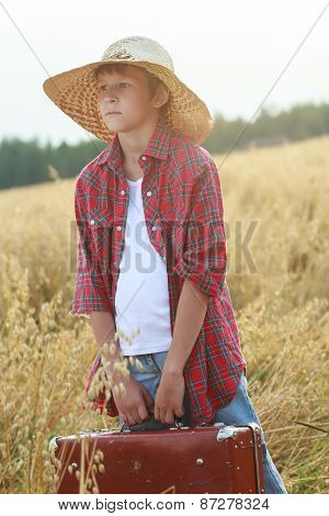 Teenage Traveler In Farm Oat Field Holding Old-fashioned Suitcase And Looking To Horizon